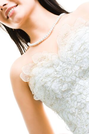 Close-up of beautiful bride in white dress and beads on her neck photo