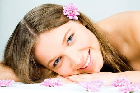 herself: Photo of a young happy woman lying in the spa salon and enjoying herself with some flowers at the front Stock Photo