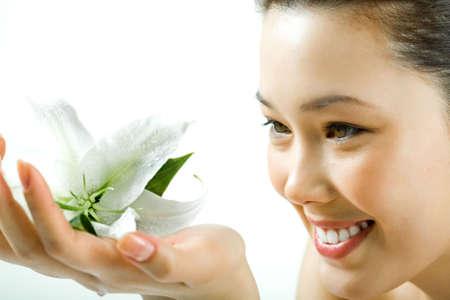 attractiveness: Closeup de la hermosa muchacha sonriente mirando a dulce lirio blanco en la mano