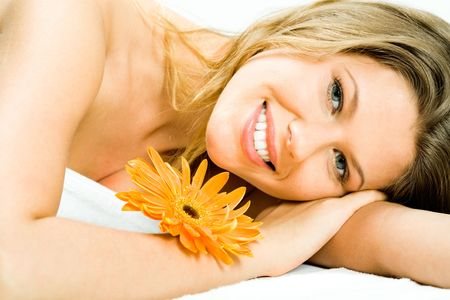 Photo of young pretty woman lying in the spa salon and enjoying aromatherapy with a flower near by photo