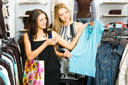 Portraits of two friends in the clothing department looking at new T-shirt and choosing new clothes photo