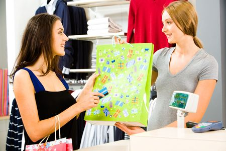 Portrait of a shop assistant holding shopping bag and a pretty girl with credit card paying for the purchase in the shopping centre Stock Photo - 2831616