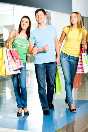 go shopping: Portrait of three people walking in the shopping mall  Stock Photo