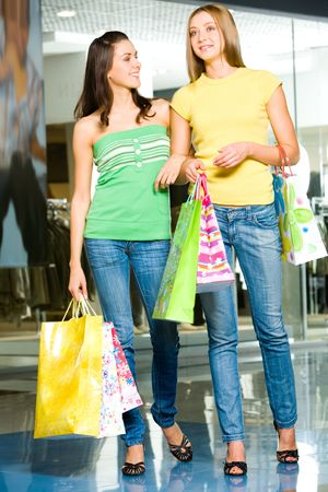 Image of two attractive women holding the bags and standing in the shopping mall photo