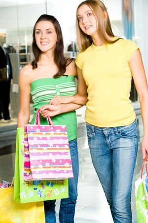 Photo of two young women carrying the shopping bags and looking at something photo