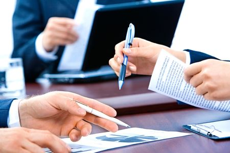 Close-up of business people�s hands holding pens and documents at meeting photo