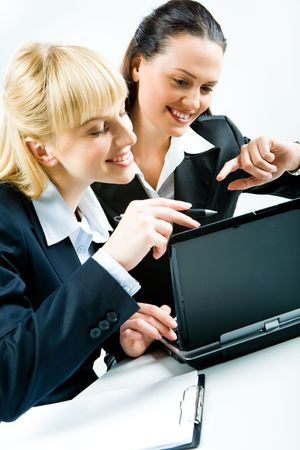 Vertical photo of two pretty businesswomen sitting at laptop and looking at its screen  photo