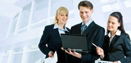 Successful businesspeople looking at the laptop screen on the background of office building photo