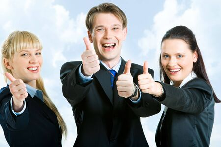 Portrait of three happy business partners holding their thumbs up on the background of blue sky photo