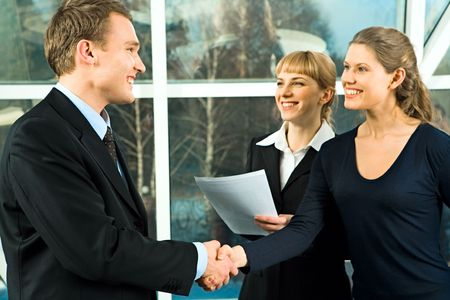 Photo of handshake of businesspeople with their smiling in the office photo