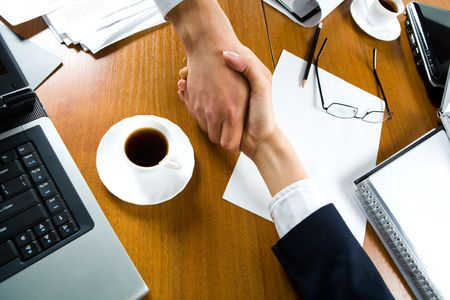 Photo of handshake of business people over the workplace