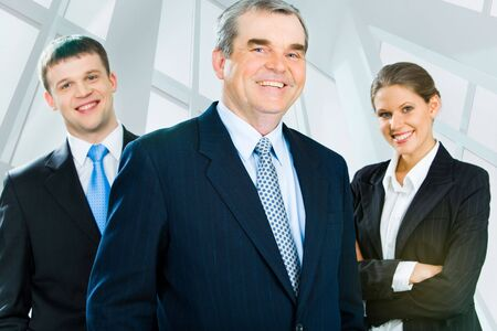 him: Portrait of senior boss looking at camera with smile with his business team standing on each side of him
