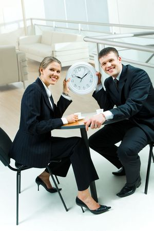 Portrait of two businesspeople sitting at table in the office and holding clock showing that it�s time for coffee break Stock Photo - 2885037