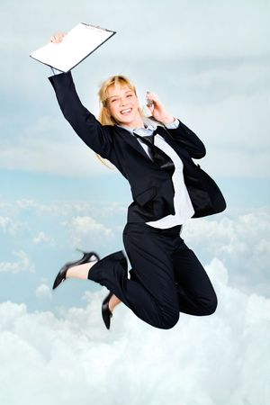 Vertical photo of very happy woman in high jump with documents and cell in hands up in the clouds