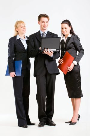 Team of three business people looking at the laptop and standing together Stock Photo - 2885024