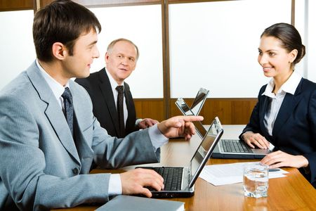 Young businessman sitting at the table near laptop and pointing into it looking at smiling businesswoman Stock Photo - 2885477