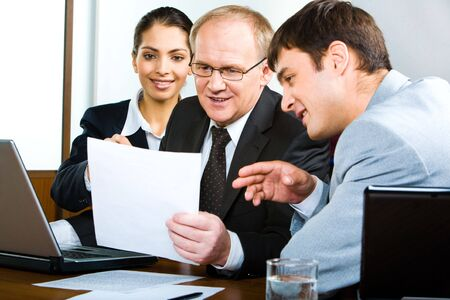 Portrait of businessteam looking at new business plan held by their senior boss and discussing it Stock Photo - 2885036