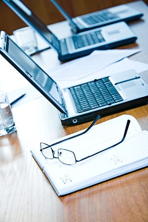 Image of glasses lying on the notepad on the background of laptops in line Stock Photo - 2885033