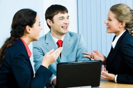 Portrait of three business partners sitting in the office and laughing during discussion of business plans Stock Photo - 2885474