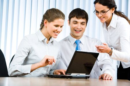 Photo of business team sitting in the office and looking at the laptop monitor during business meeting Stock Photo - 2885464