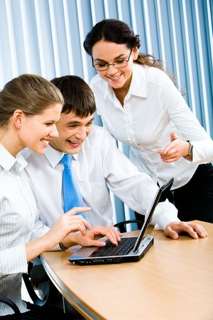 Vertical image of group of three business people looking at laptop monitor with smart woman pointing at it Stock Photo - 2885466