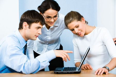 Portrait of serious businessman sitting at the table and pointing at the laptop monitor with two smiling ladies near by Stock Photo - 2885038