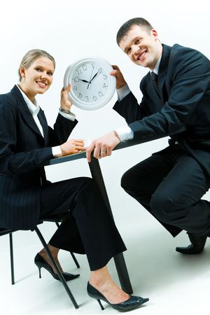 Image of business people holding the clock together and smiling  photo