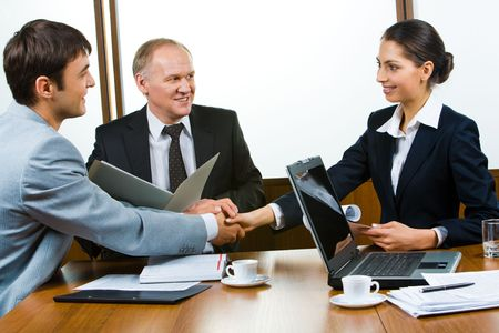 consensus: Photo of business partners holding hands making a consensus Stock Photo