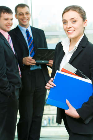 Portrait of business woman holding the folders on the background of businessmen photo