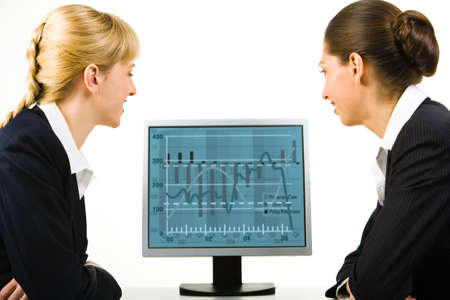 Portrait of two business ladies looking into the computer screen  photo