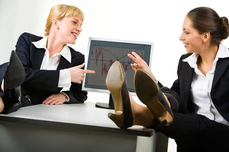Photo of two relaxed business ladies sitting at table with their legs on it and pointing at the computer screen photo