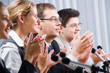 applauding: Row of successful applauding young people in office