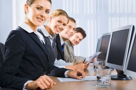 Portrait of confident people sitting in a line in front of monitors and looking at camera Stock Photo - 2913182