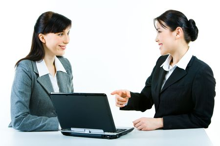 Portrait of two smiling business ladies sitting at laptop while one of the women pointing at its screen Stock Photo - 2913213