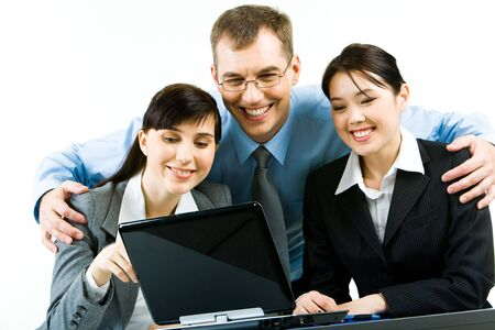 Portrait of smiling young woman sitting at the table with their leader standing behind them and looking at laptop screen together Stock Photo - 2913219