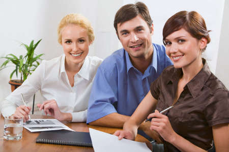 Confident business people looking at camera in a working environment photo