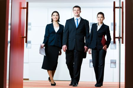 woman handle success: Photo of group of business partners standing in front of open doors and going to enter conference hall Stock Photo