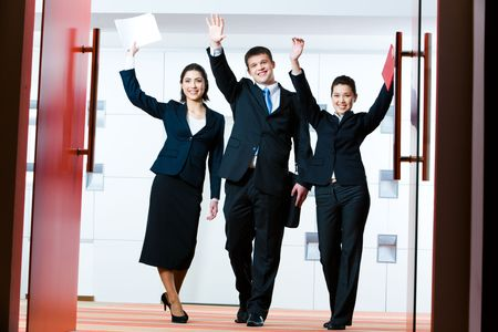 Portrait of successful business group standing at the door of conference hall with raised hands greeting their partners photo
