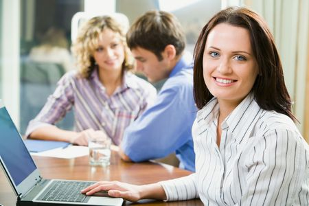 Young smart smiling woman sitting at the table and typing on her laptop Stock Photo - 2937713