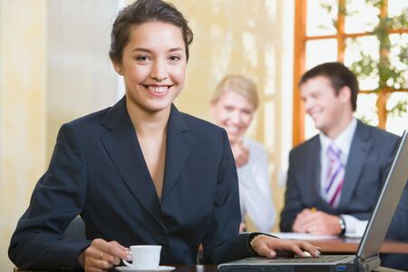 Portrait of smiling woman looking at camera on the background of two business people Stock Photo - 2937851
