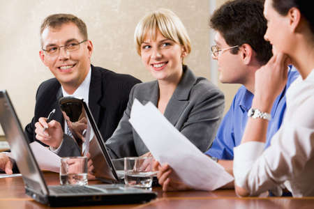 Four confident specialists gathered together for discussion of new strategy of business photo