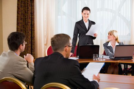 Businesspeople sitting at the table listening to their colleague�s speech in conference room photo