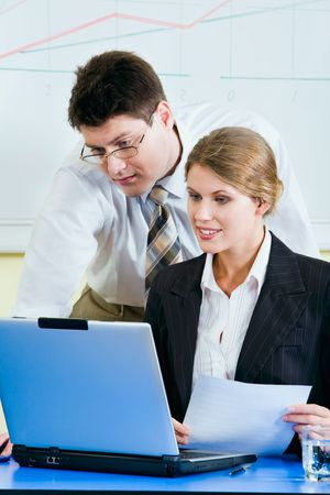 Successful businessman is looking in the laptop with his colleague  photo