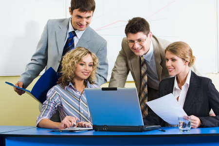 Portrait of four successful people gathered together around the laptop and gazing at the monitor Stock Photo - 2948744