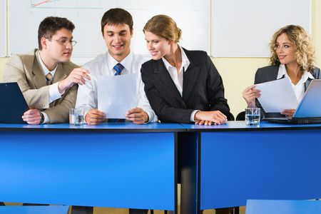 Group of people sitting at the blue table and discussing business questions in the room Stock Photo - 2948718