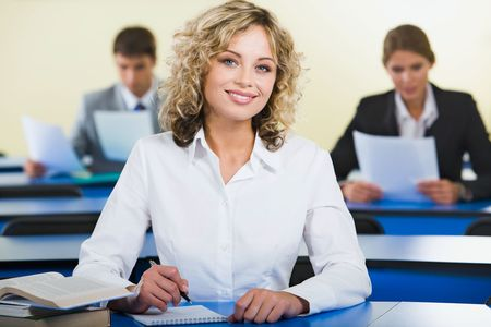 successful student: Successful student is writing a text and sitting at the table with books Stock Photo