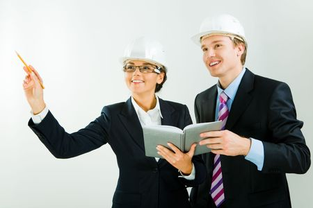 Image of business woman raising her hand and holding notepad together with worker standing near by photo