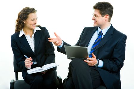 Portrait of two successful business partners sitting and looking at each other with smiles at meeting: man with laptop, woman holding pen and notebook photo