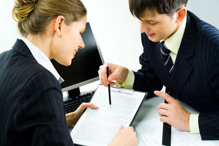 Close-up of two confident colleagues looking at document attentively while man pointing at some piece of text in it with pencil photo
