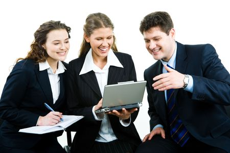 Portrait of businesswoman sitting with laptop in hands while her partners looking at its screen with smiles photo